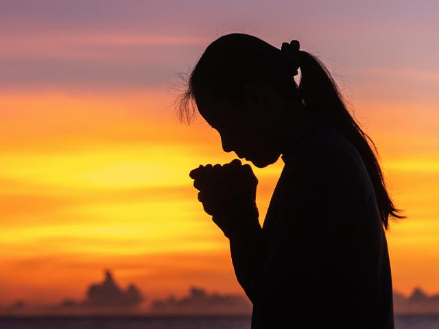 silhouette of a woman crying and praying
