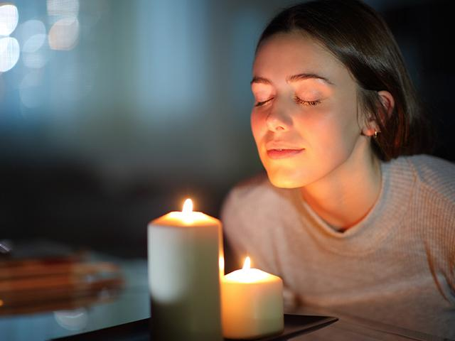 woman smelling scented candle
