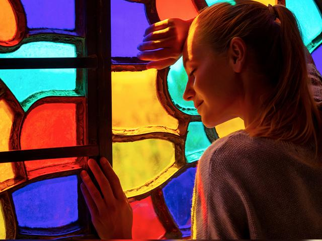 young woman leaning her head on pretty stained glass window