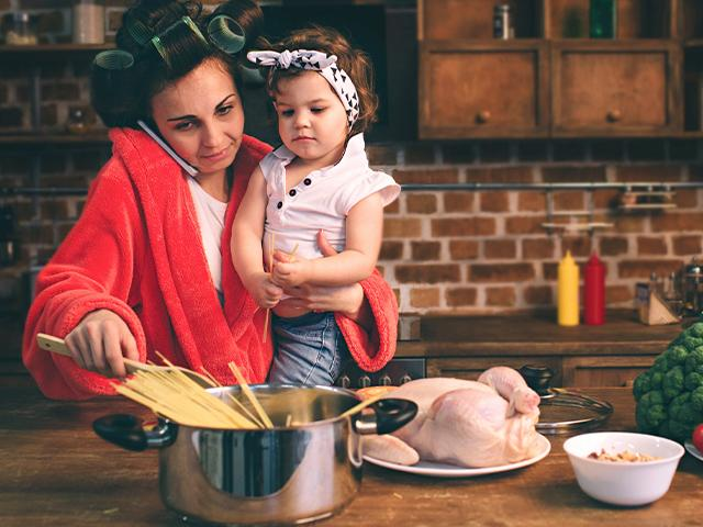 stressed mom with a baby on her hip in the kitchen