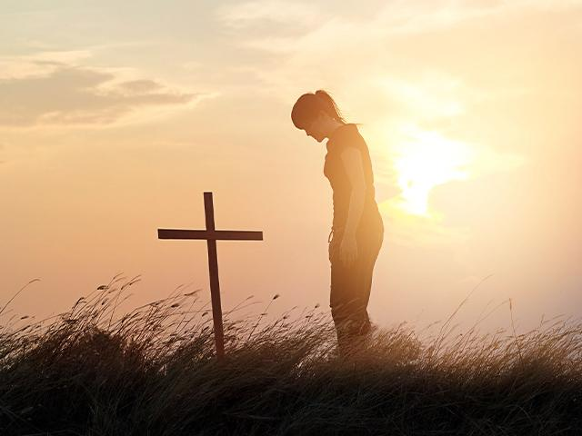 woman showing respect for the cross on a hill at sunset