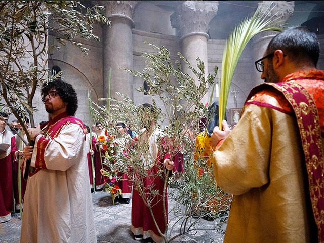 Armenian clergy hold olive tree branches and palm fronds during the Palm Sunday procession at the Church of the Holy Sepulchre. (AP Photo/Oded Balilty)