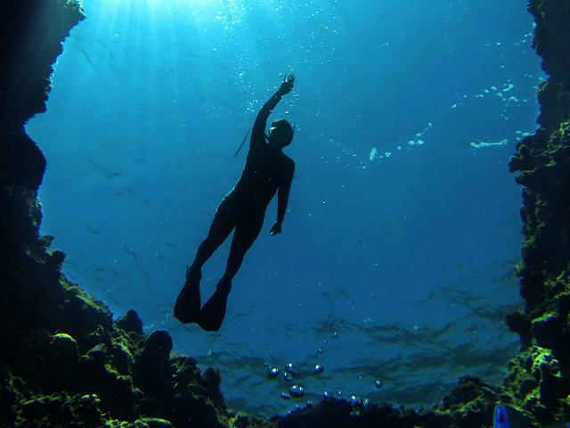 underwater diver swimming in a cave