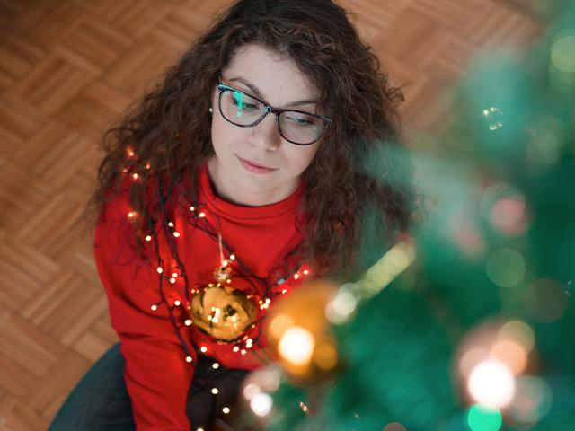 woman sitting beside Christmas tree looking lonely
