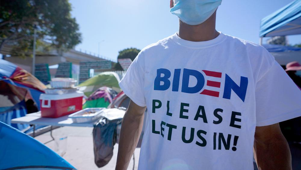 "A Honduran man seeking asylum in the U.S. wears a shirt that reads, ""Biden please let us in,"" as he stands near an entrance to the border crossing, March 1, 2021, in Tijuana, Mexico. (AP Photo/Gregory Bull)"