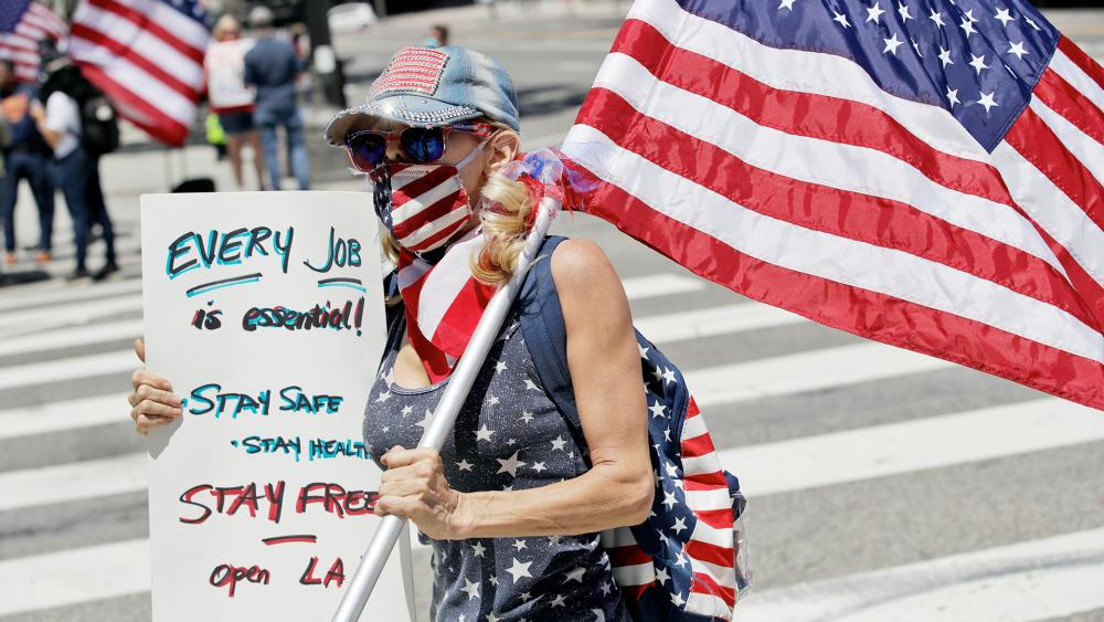 A protester holds a sign during a rally calling for an end to Gov. Gavin Newsom's stay-at-home orders amid the COVID-19 pandemic, April 22, 2020, outside of city hall in downtown Los Angeles. (AP Photo/Marcio Jose Sanchez)