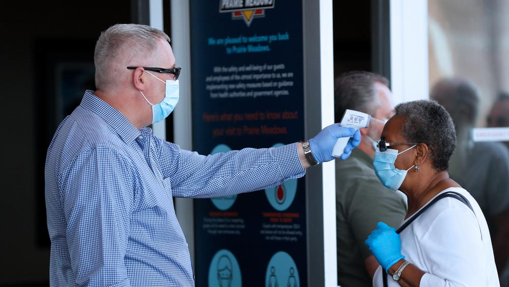 A women has her temperature taken before entering Prairie Meadows Casino, June 15, 2020, in Altoona, Iowa. The casino reopened with new safety standards in place after being closed for three months due to the pandemic. (AP Photo/Charlie Neibergall)