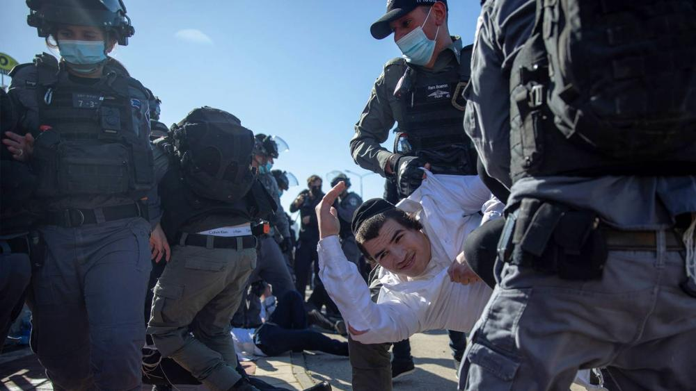 Israeli police officers clash with ultra-Orthodox Jews in Ashdod, Israel, Sunday, Jan. 24, 2021. (AP Photo/Oded Balilty)