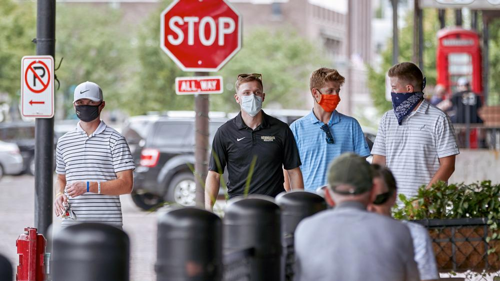 Pedestrians with face masks walk past diners in downtown Omaha, Neb., Aug. 7, 2020. (AP Photo/Nati Harnik)