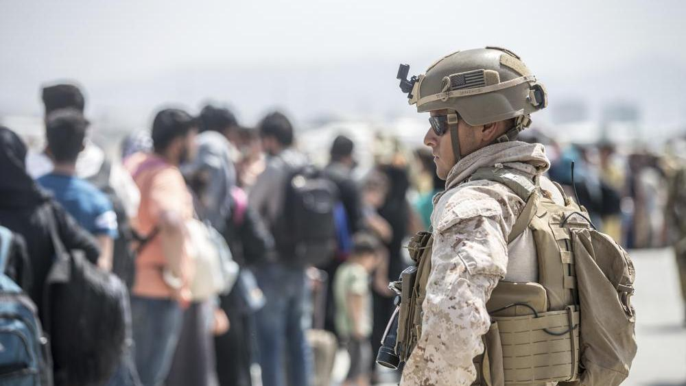 A Marine with Special Purpose Marine Air-Ground Task Force-Crisis Response-Central Command provides assistance during an evacuation at Kabul Airport (Sgt. Samuel Ruiz/U.S. Marine Corps via AP)