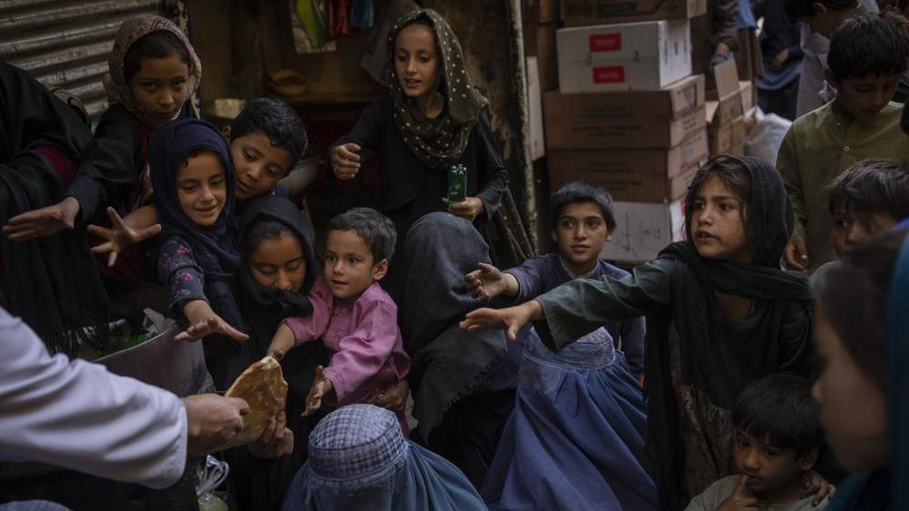 Afghan women and children receive bread donations in Kabul's Old City, Afghanistan, Thursday, Sept. 16, 2021. (AP Photo/Bernat Armangue)