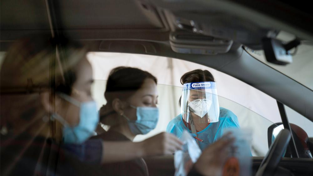 Medical assistant Linh Nguyen assists two women with COVID-19 testing at a testing site set up at the OC Fairgrounds in Costa Mesa, Calif., Nov. 16, 2020. (AP Photo/Jae C. Hong)