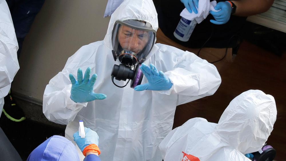 Cleaning workers are sprayed as they exit the Life Care Center in Kirkland, Wash., Thursday, March 12, 2020, at the end of a day spent cleaning inside the facility near Seattle. (AP Photo/Ted S. Warren)