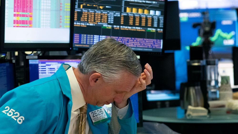 A trader holds his hand to his head after trading was halted at the New York Stock Exchange, Wednesday, March 18, 2020, in New York. (AP Photo/Mark Lennihan)