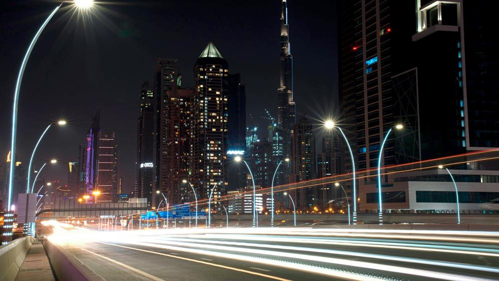 In this photo taken with a slow shutter speed, traffic speeds down the Sheikh Zayed Road in Dubai, United Arab Emirates, Monday, July 6, 2020. (AP Photo/Jon Gambrell)