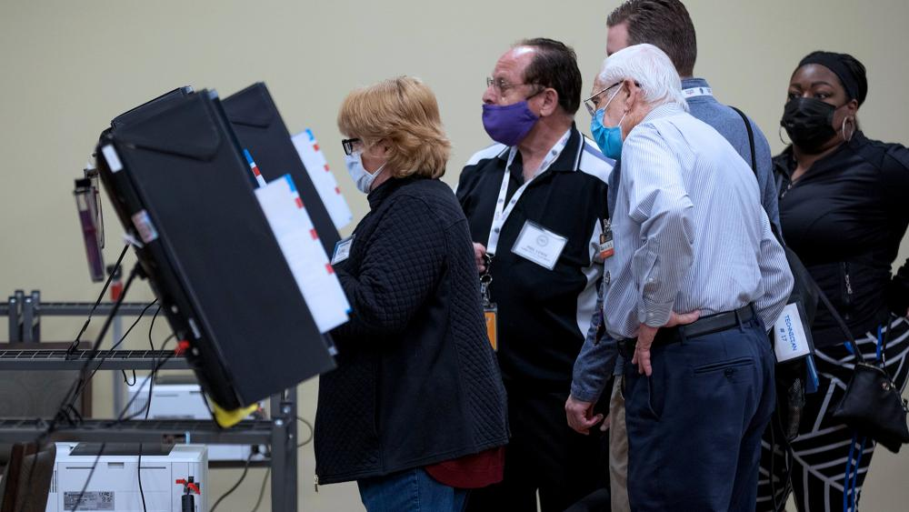Poll workers and technicians try to get machines up and running after experiencing issues during Georgia's Senate runoff elections at a senior center, Tuesday, Jan. 5, 2021, in Acworth, Ga. (AP Photo/Branden Camp)