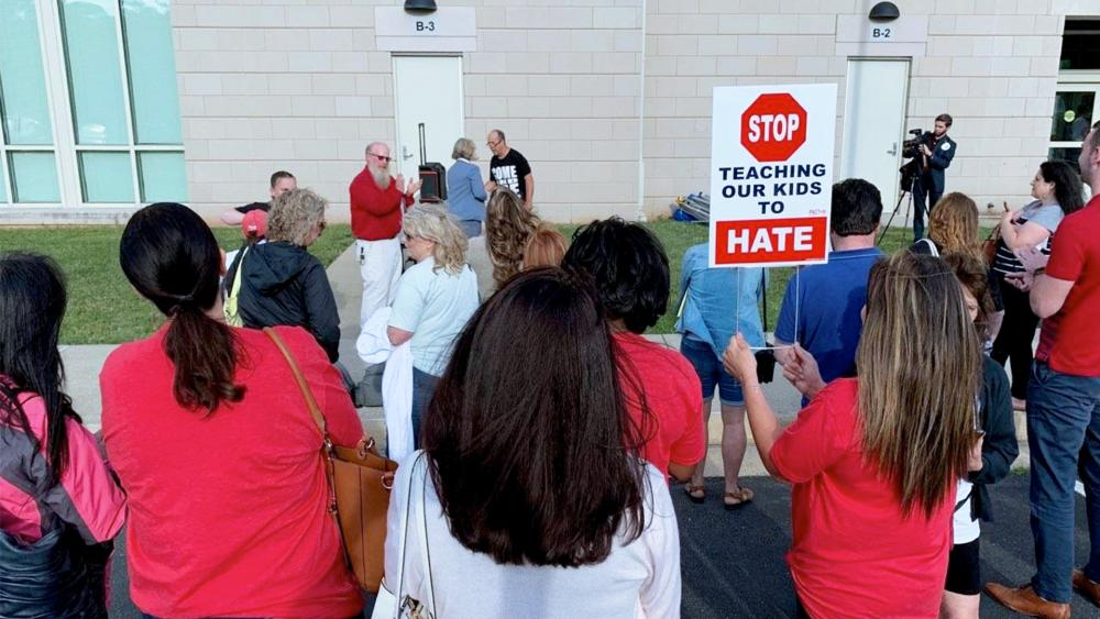 """Parents protest the school board's support for Critical Race Theory with a sign saying: """"Stop teaching our kids to hate."""" (Image: Tara Mergener, CBN News)"""