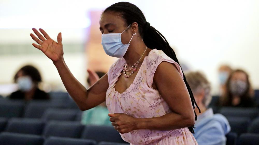 Sonia Falk prays during a Memorial Day service at Lakewood Chapel Church in Arlington Heights, Ill., Sunday, May 24, 2020 (AP Photo/Nam Y. Huh)