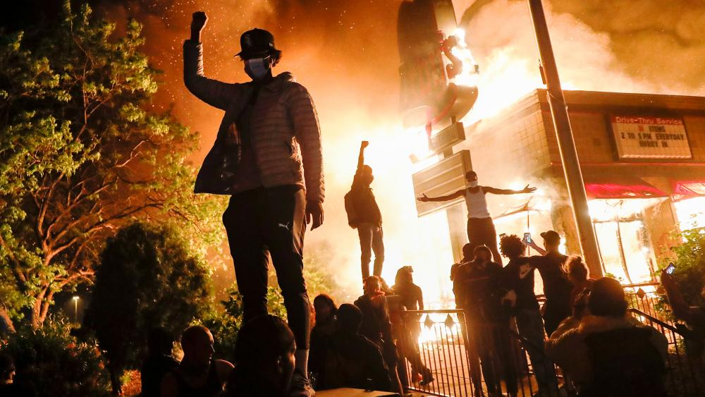 Protestors riot outside of a burning fast food restaurant, May 29, 2020, in Minneapolis after the death of George Floyd, a black man who died in police custody. (AP Photo/John Minchillo)