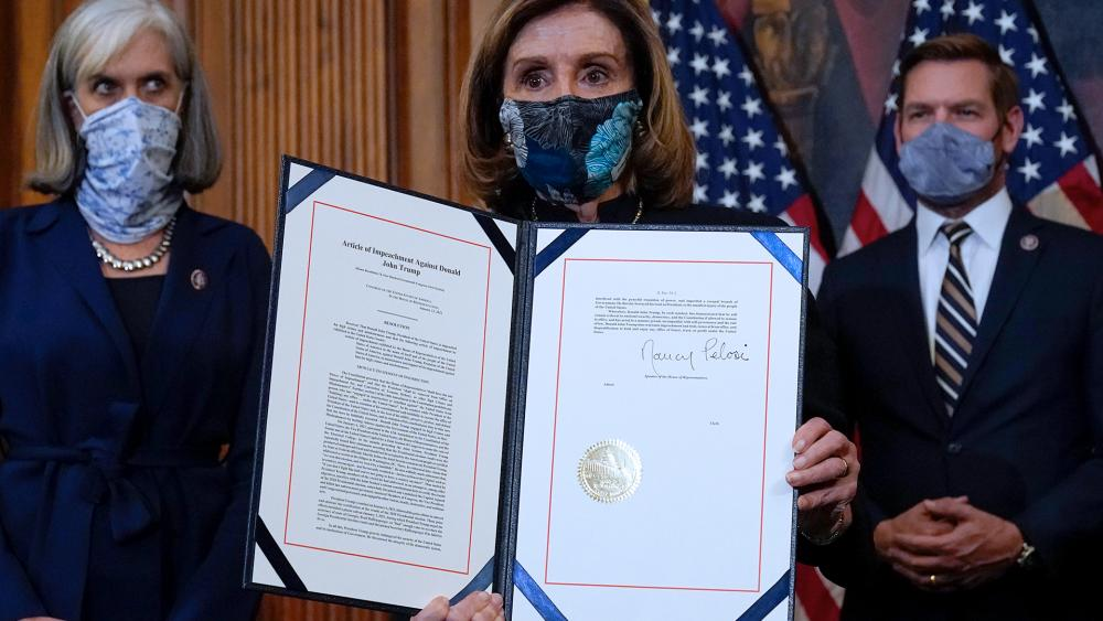 House Speaker Nancy Pelosi (D-CA) displays the article of impeachment that she signed against President Donald Trump, Wednesday, Jan. 13, 2021. (AP Photo/Alex Brandon)