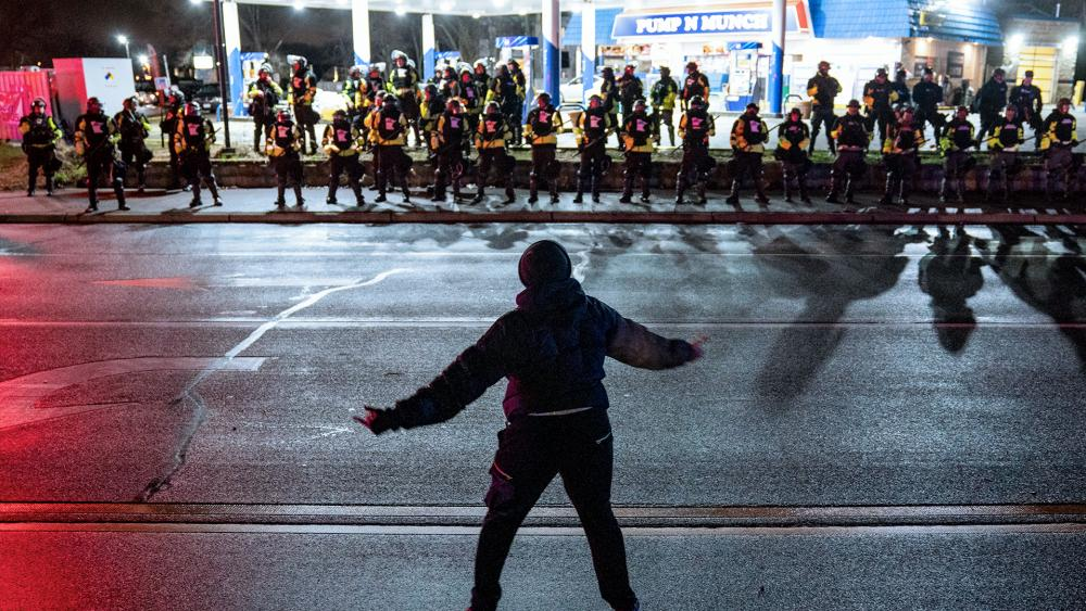 Demonstrator stands in front of authorities who advanced into a gas station after issuing orders for crowds to disperse during a protest (AP Photo/John Minchillo)