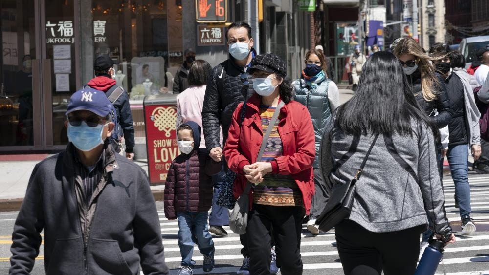 People walk on the street, Monday, April 26, 2021 in New York. (AP Photo/Mark Lennihan)