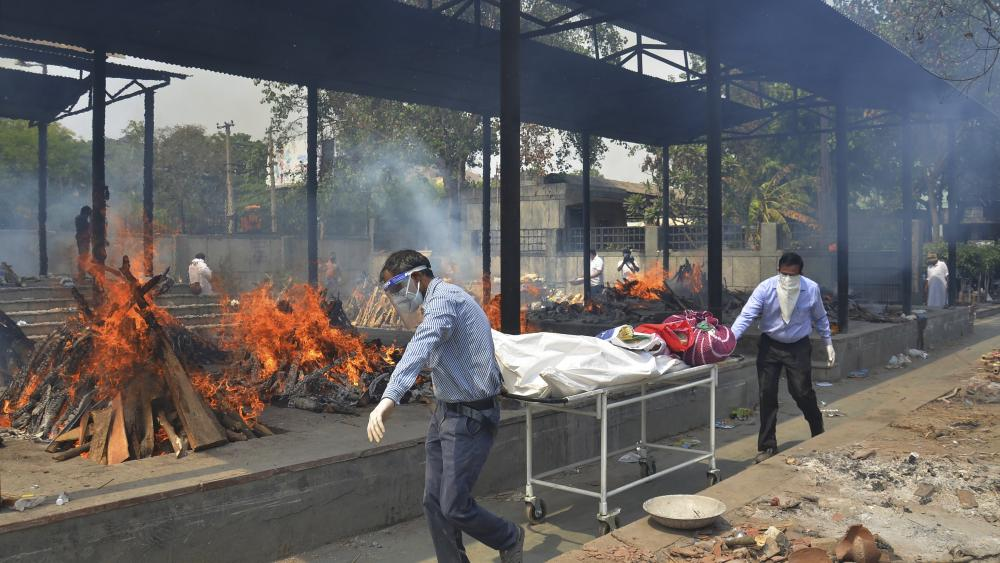 In this May 1, 2021, file photo, relatives carry the body of a person who died of COVID-19 as multiple pyres of other COVID-19 victims burn at a crematorium in New Delhi, India. (AP Photo/Amit Sharma, File)