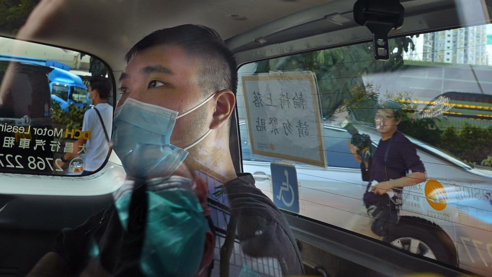 FILE - In this July 6, 2020, file photo, Tong Ying-kit arrives at a court in a police van in Hong Kong. (AP Photo/Vincent Yu,File)