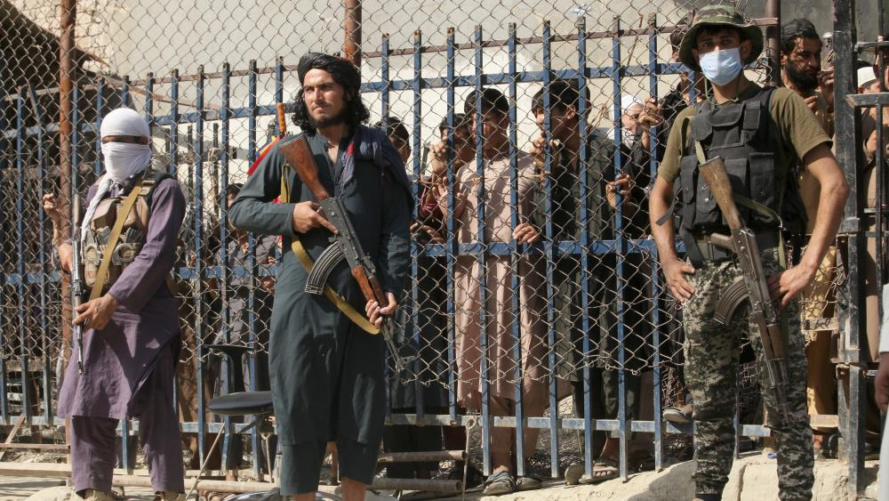 A Pakistani paramilitary soldier, right, and Taliban fighters stand guard on their respective sides at a border crossing point between Pakistan and Afghanistan, in Torkham, in Khyber district, Pakistan, Saturday, Aug. 21, 2021.(AP Photo/Muhammad Sajjad)