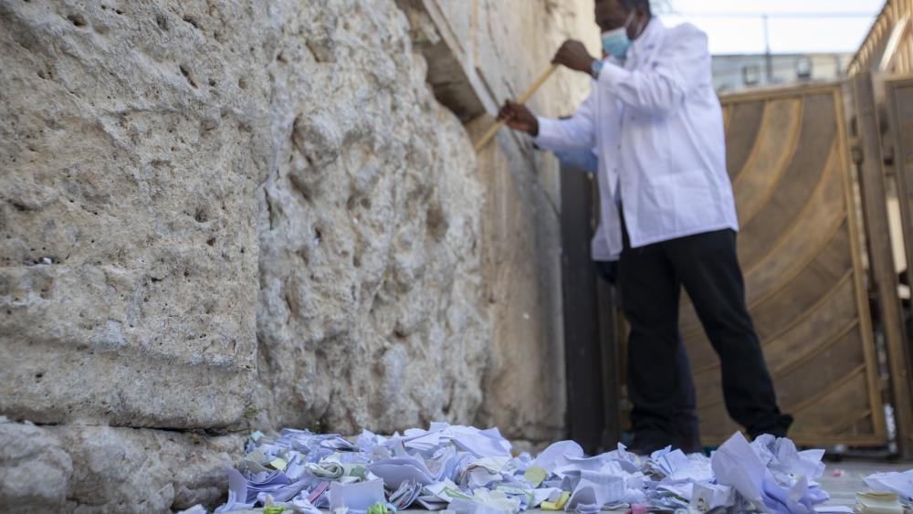 A worker removes prayer notes left by visitors from a gap between the stones on the Western Wall.(AP Photo/Ariel Schalit)