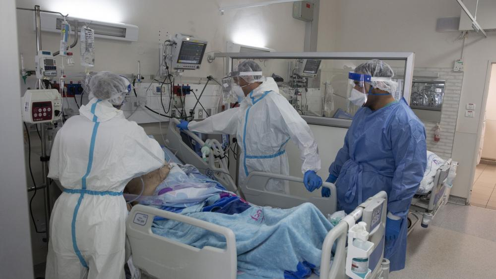 Medical professionals tend to an elderly man after they took him off of a breathing machine in the coronavirus ward at Barzilai Medical Center in Ashkelon, Israel, Thursday, Aug. 26, 2021. (AP Photo/Maya Alleruzzo)