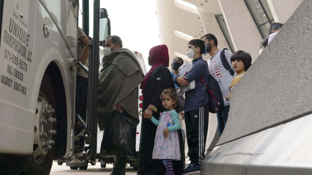 Families evacuated from Kabul, Afghanistan, wait to board a bus after they arrived at Washington Dulles International Airport, in Chantilly, Va., on Thursday, Aug. 26, 2021. (AP Photo/Jose Luis Magana)