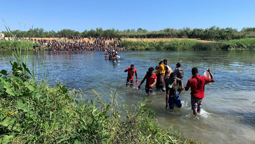 Migrants find an alternate place to cross from Mexico to the United States after access to a dam was closed, Sunday, Sept. 19, 2021, in Ciudad Acuña, Mexico.(AP Photo/Sarah Blake Morgan)