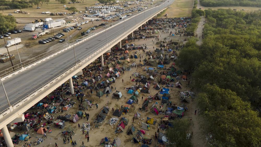 Migrants, many from Haiti, are seen at an encampment along the Del Rio International Bridge near the Rio Grande, Tuesday, Sept. 21, 2021, in Del Rio, Texas. (AP Photo/Julio Cortez)