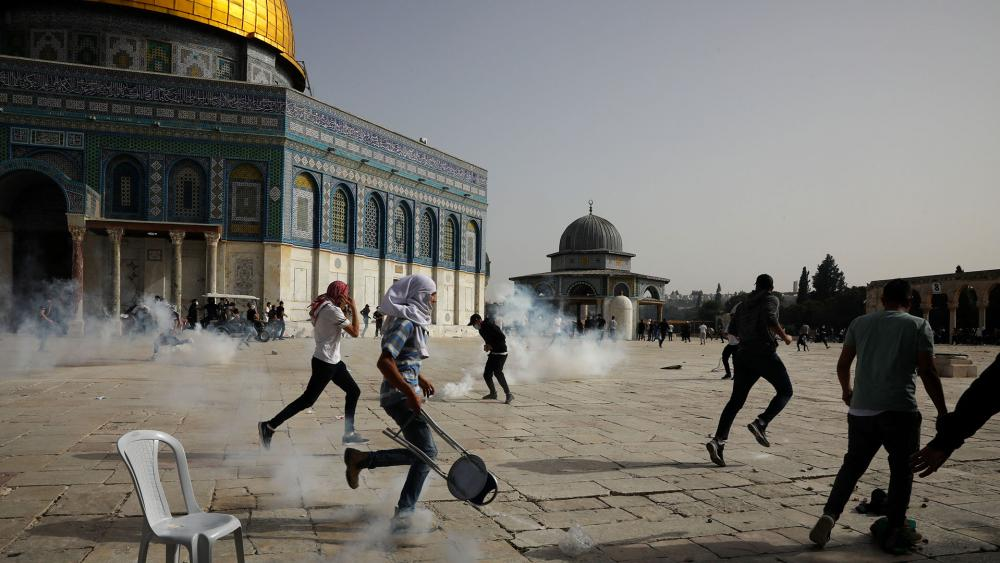 Palestinians run away from tear gas during clashes with Israeli security forces at the Al Aqsa Mosque compound in Jerusalem's Old City Monday, May 10, 202. (AP Photo/Mahmoud Illean)