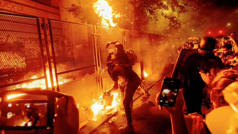 Protesters throw flaming debris over a fence at the Mark O. Hatfield US Courthouse in Portland, Ore. (AP Photo/Noah Berger)